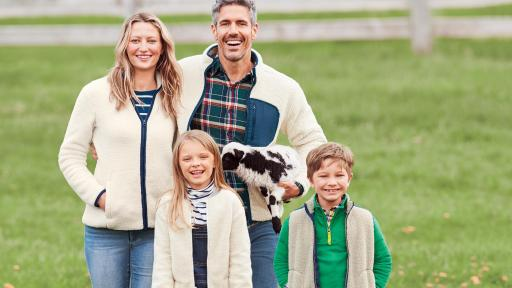 Family wearing Lands Ends Sherpa outerwear, standing outside with baby sheep nearby
