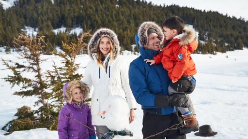 Family outdoors in the snow, wearing Lands End outerwear.