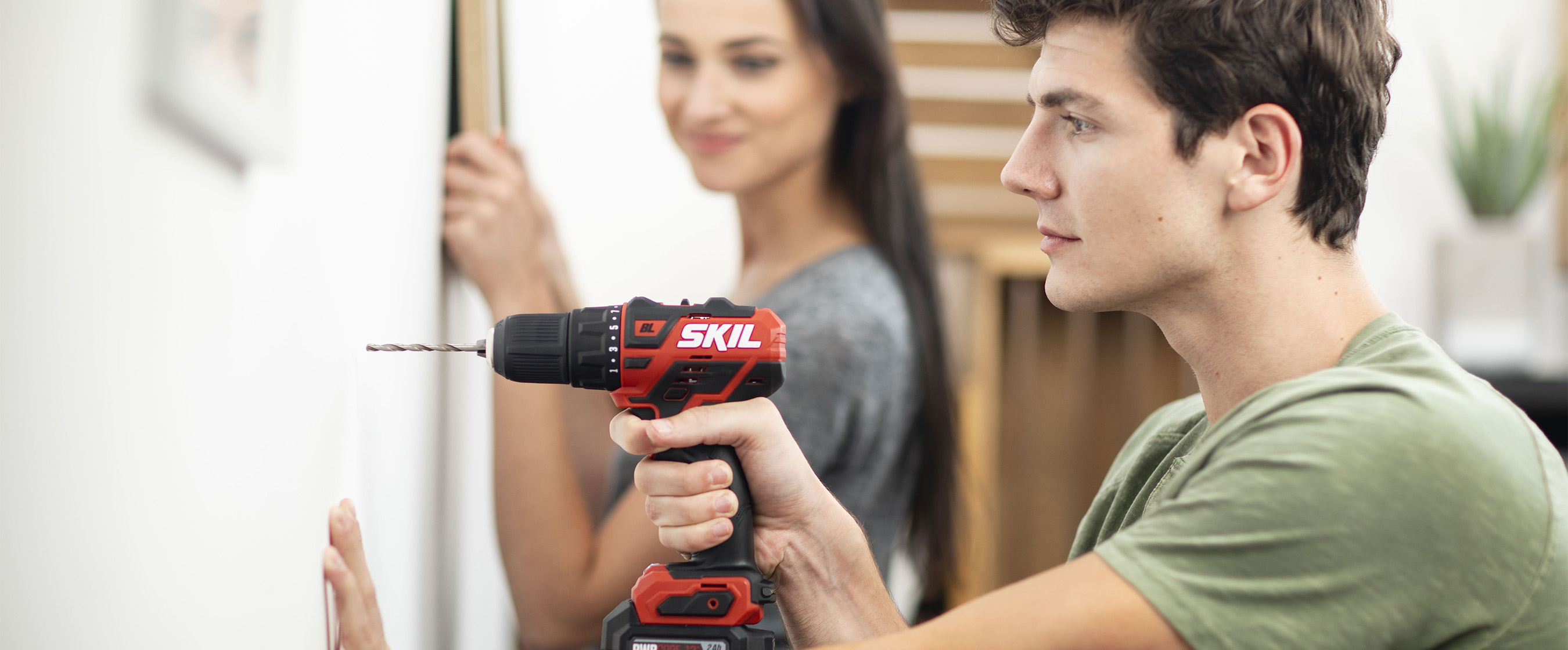 Man using a SKIL Drill Driver while woman watches