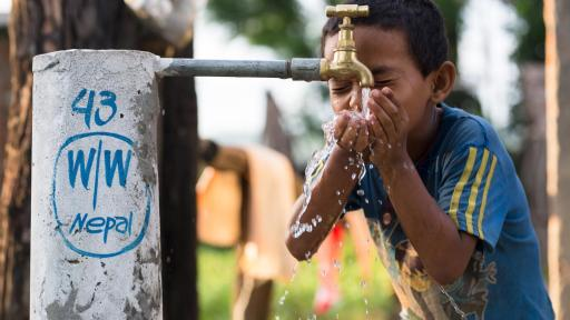 Boy drinking water from spout outside