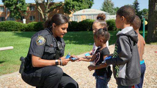 Female cop handing out Hershey's bars to children in neighborhood