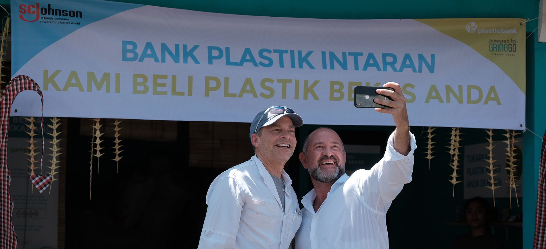 David Katz taking a selfie in front of the Plastic Bank Opening sign
