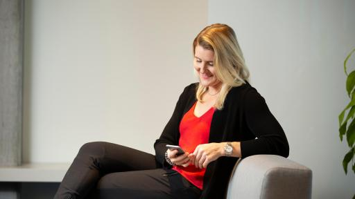Hayley Wickenheiser sitting on sofa looking at iphone