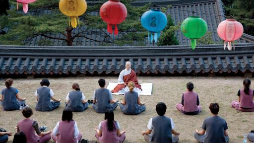 Meditators sitting outdoors, colorful paper lamps sit above them.