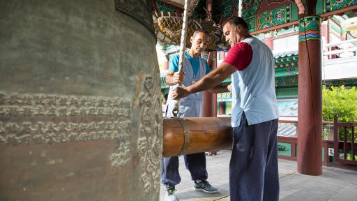Two men ringing a very large temple bell.