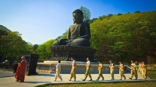 Meditators walking around a giant outdoor statue of the Buddha