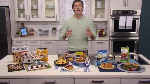 A man presents frozen food items sitting on a table in front of him