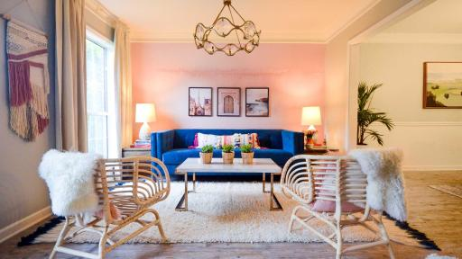 The living room, designed by Brittany Hayes of Addison's Wonderland, features an inviting velvet couch in front of a light pink temporary wallpaper mural