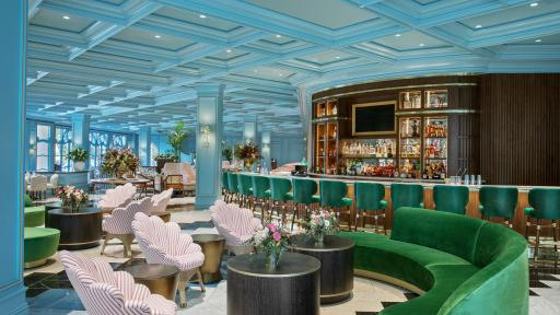 Sadelle's Interior highlighting the bar and old european style with velvet green chairs and couches and a teal ceiling.