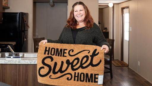 Woman holds up a home sweet home doormat