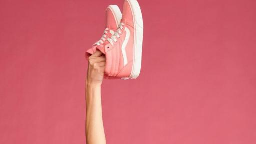 Woman holding up pink shoes