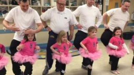 Dads dancing with their young daughters wearing tutus.