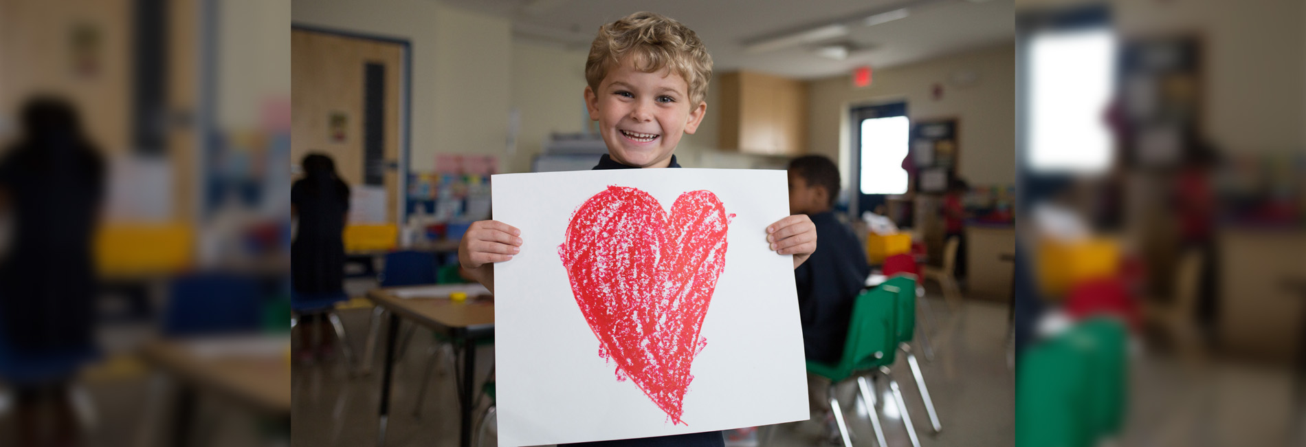 Boy holding up a drawing of a heart