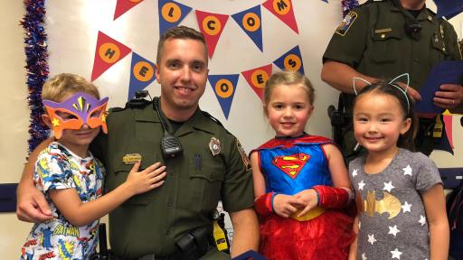 Deputy poses with three children in costumes.