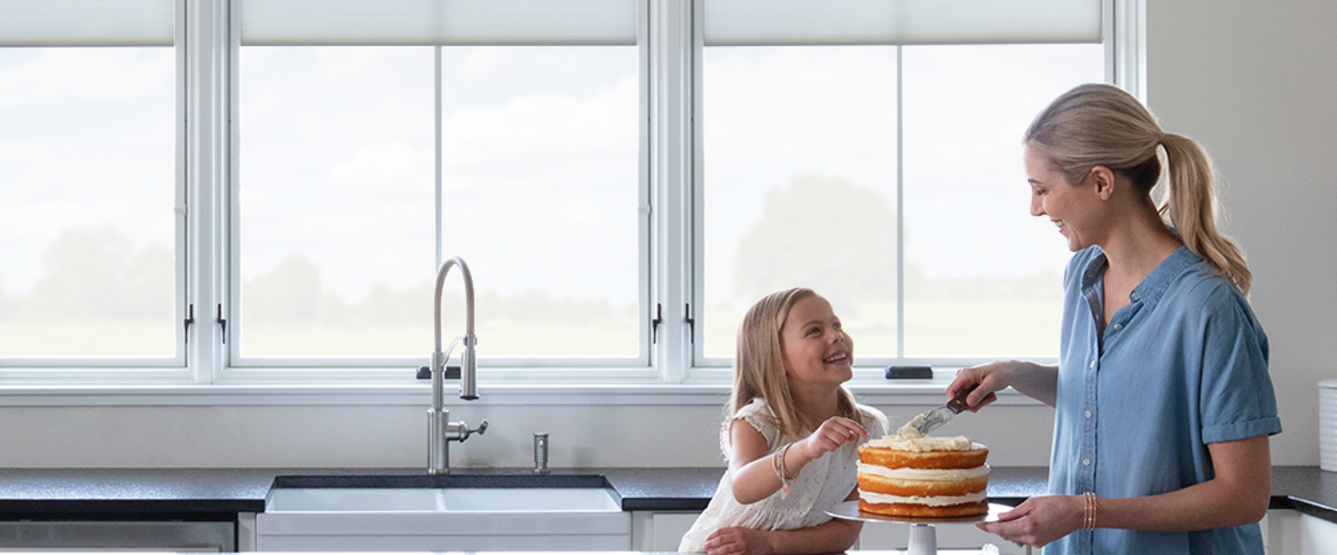 Mother and daughter icing a cake in a kitchen with Pella windows