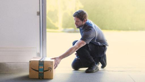 Amazon delivery driver putting a package in a garage.