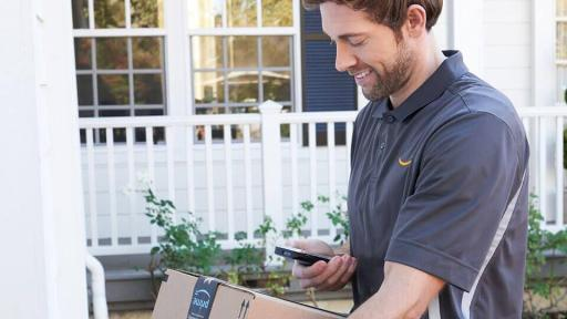 Man with an Amazon package looking at his cell phone.