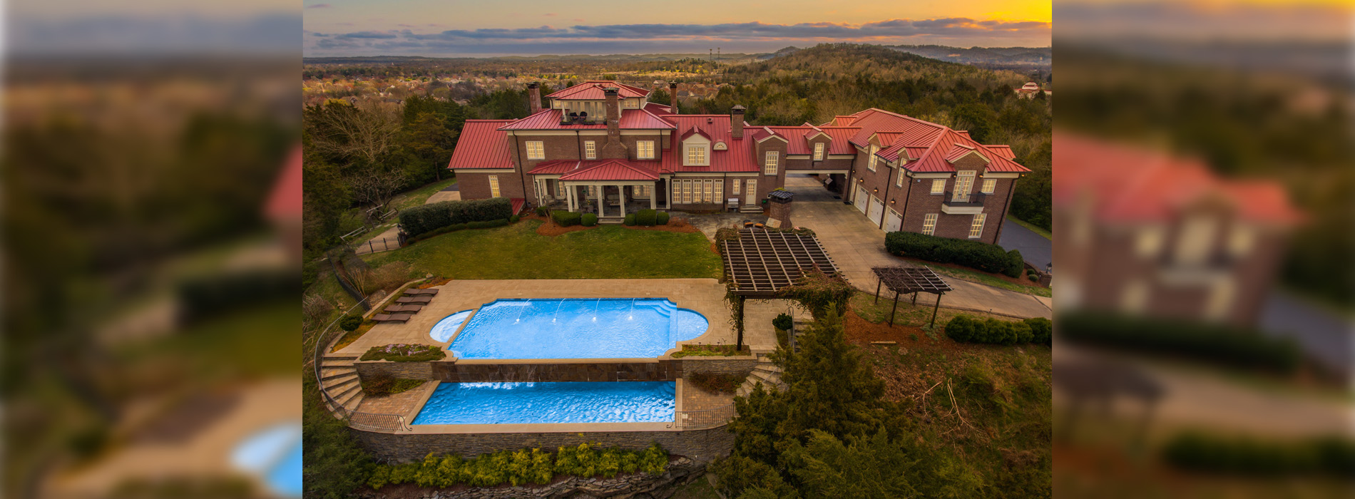 Large sprawling mansion with swimming pool in the dusk.