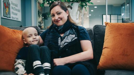 A mother sits on a couch with her son who is bald from chemotherapy.