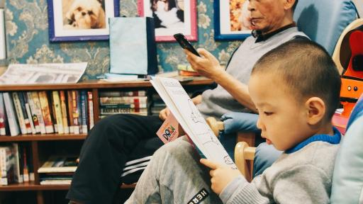 An older man and a young child sitting in a room reading books.