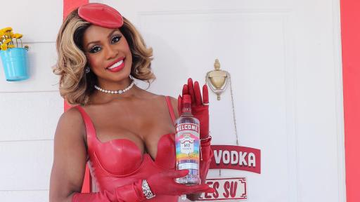 Woman in red dress holding a bottle of Smirnoff