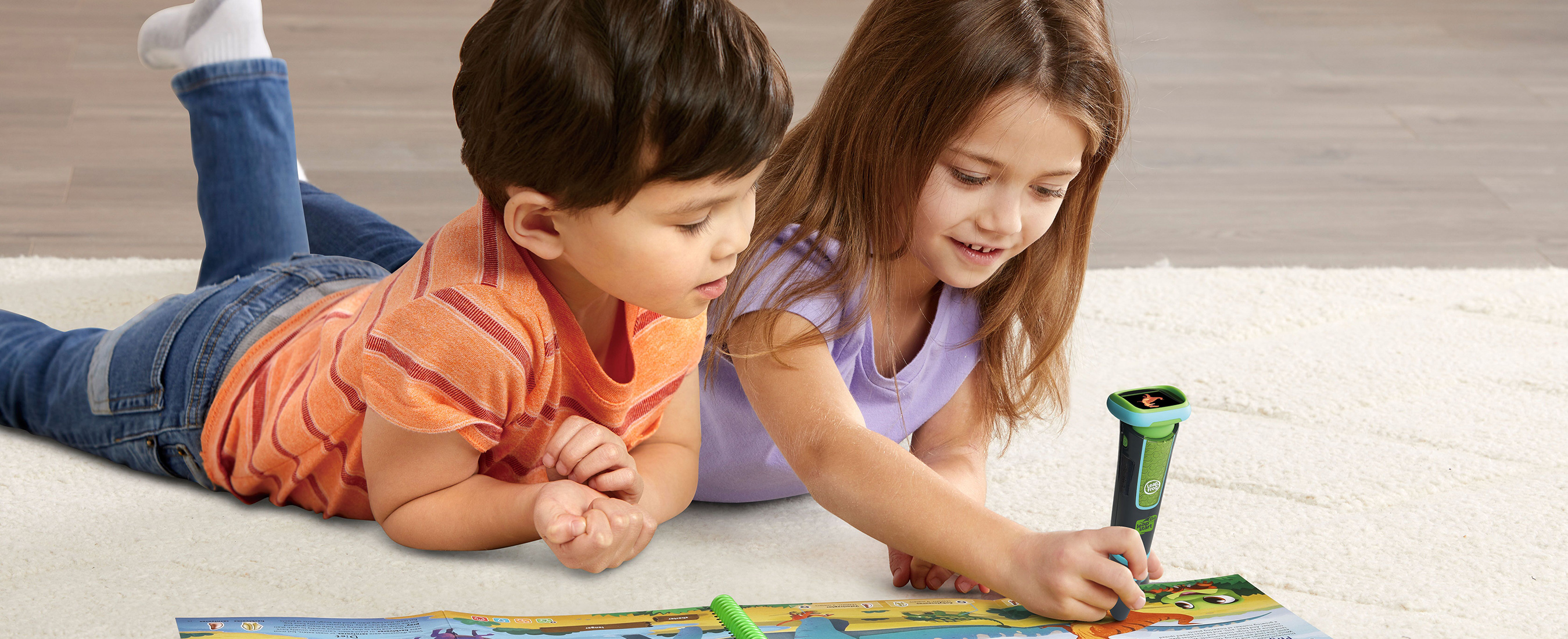 Two children playing with a book and pen