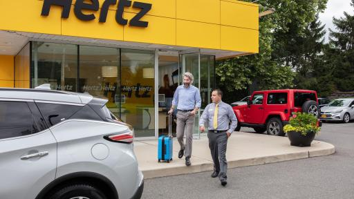 Two men walking to a Hertz Rent a car.