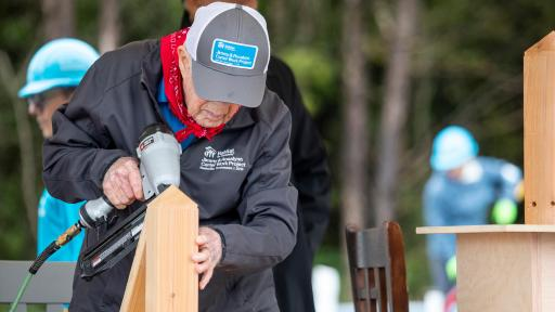 Jimmy Carter hammering two boards together for a house.