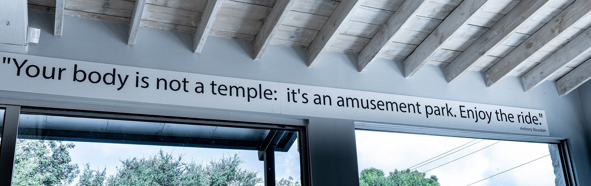 "Sign above a door that says ""Your body is not a temple: it's an amusement park. Enjoy the ride."""