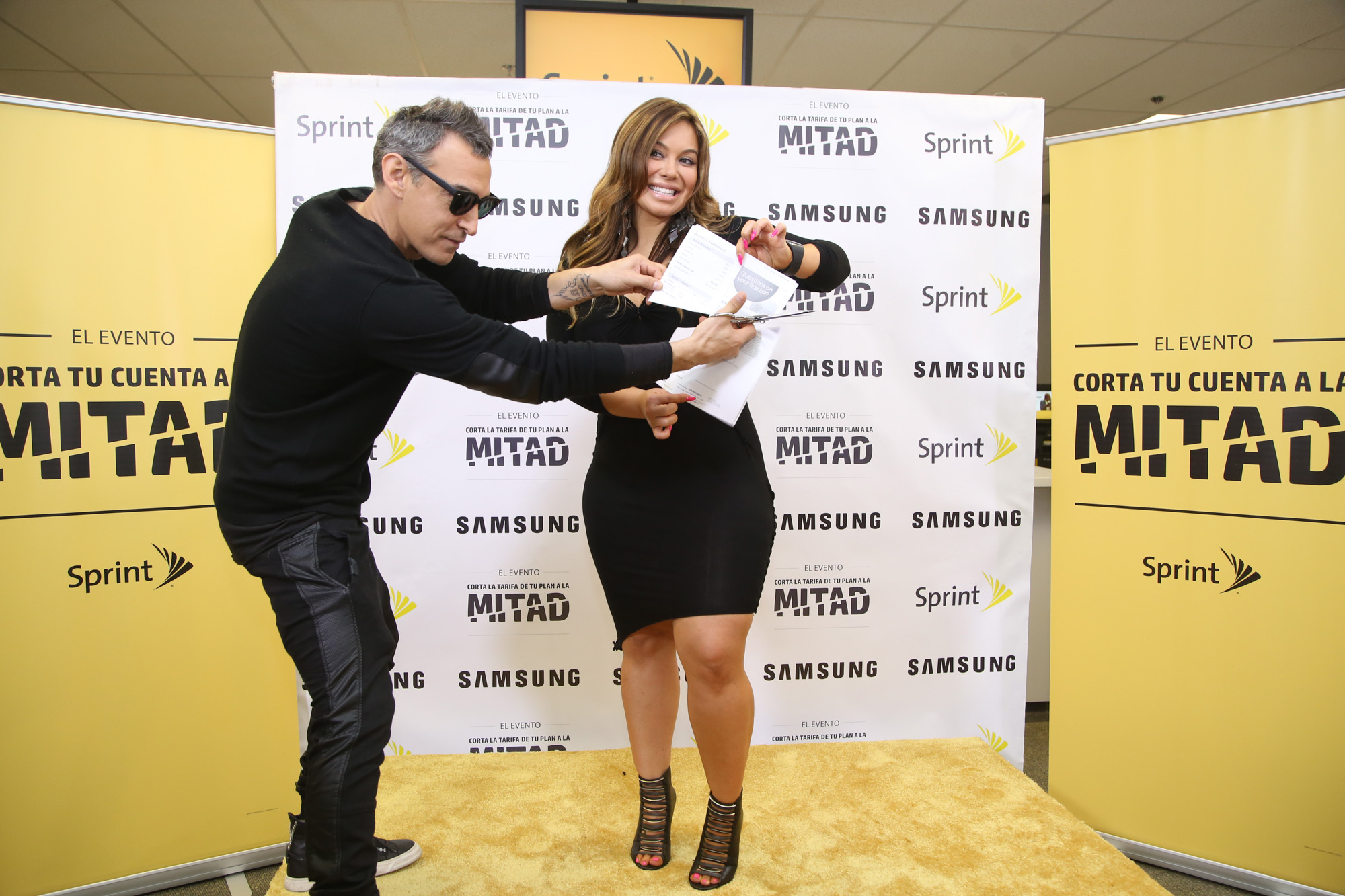 Designer to the stars, Adam Saaks and Chiquis Rivera energetically cut the competition's bill in half as part of the Sprint Cut Your Bill in Half Event.