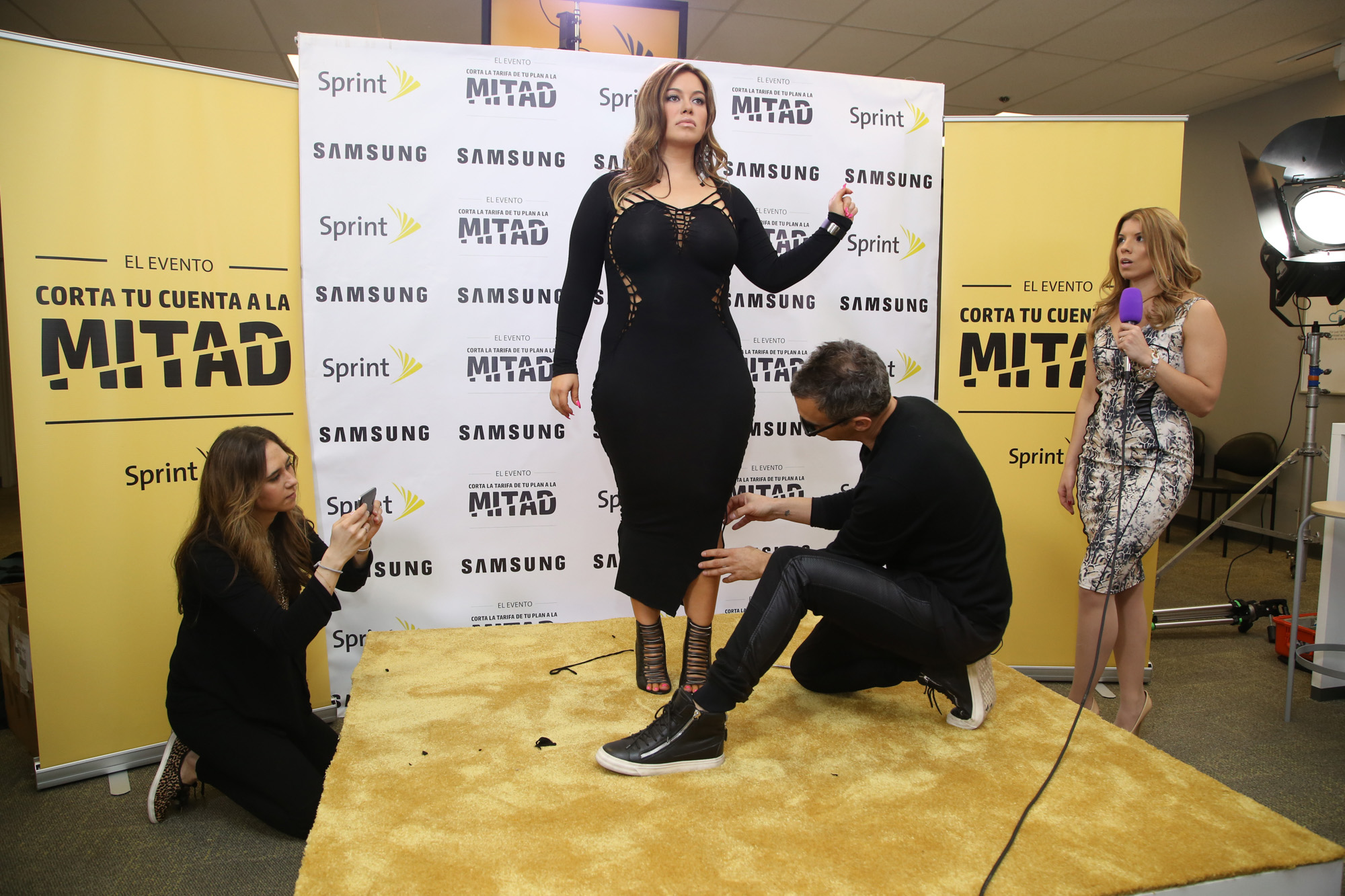 Chiquis Rivera poses while designer to the stars, Adam Saaks transforms her dress into a work of art for the Sprint Cut Your Bill in Half Event.