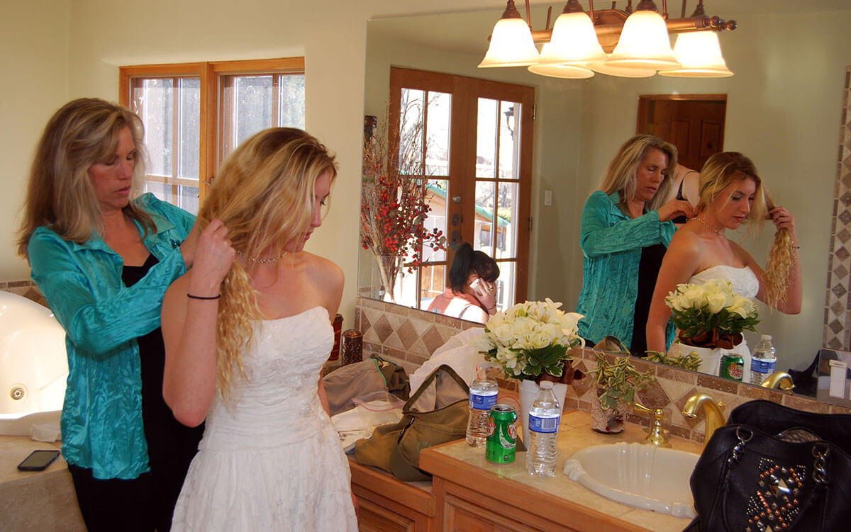 mother helping daughter get ready for her wedding