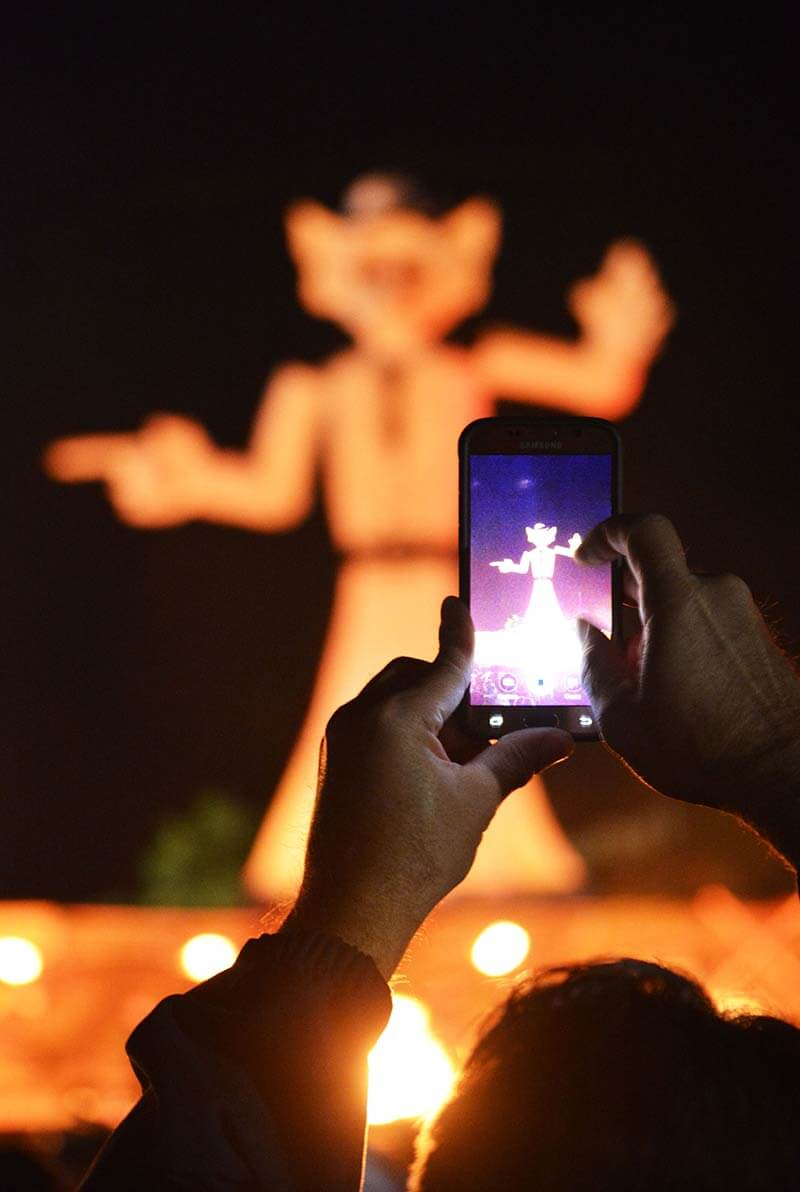 person taking a photo of zozobra