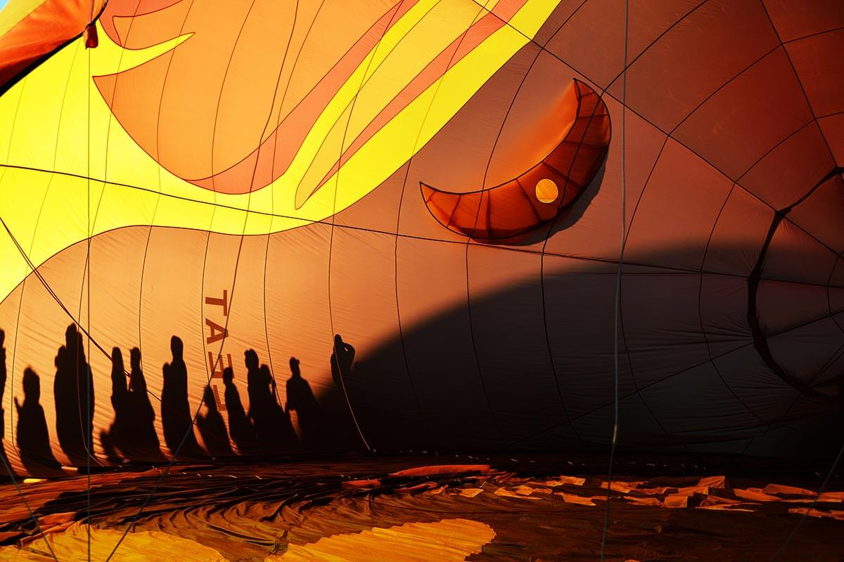 silhouette of people on a hot air balloon at night