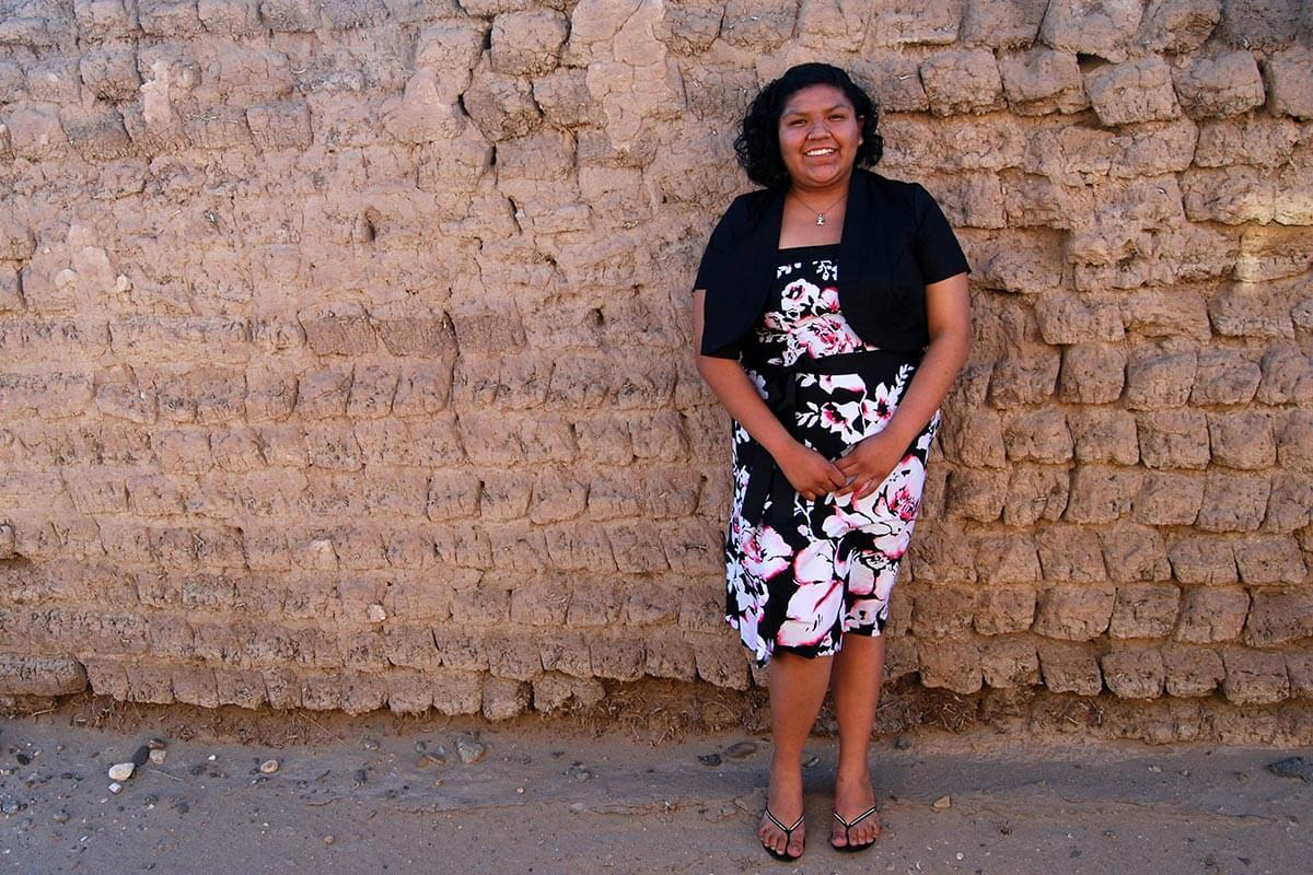 girl posing in front of an adobe wall
