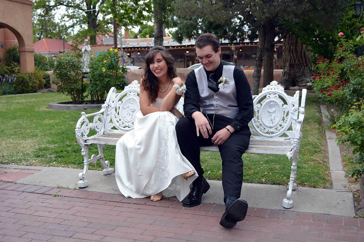 bride and groom sitting on a bench laughing
