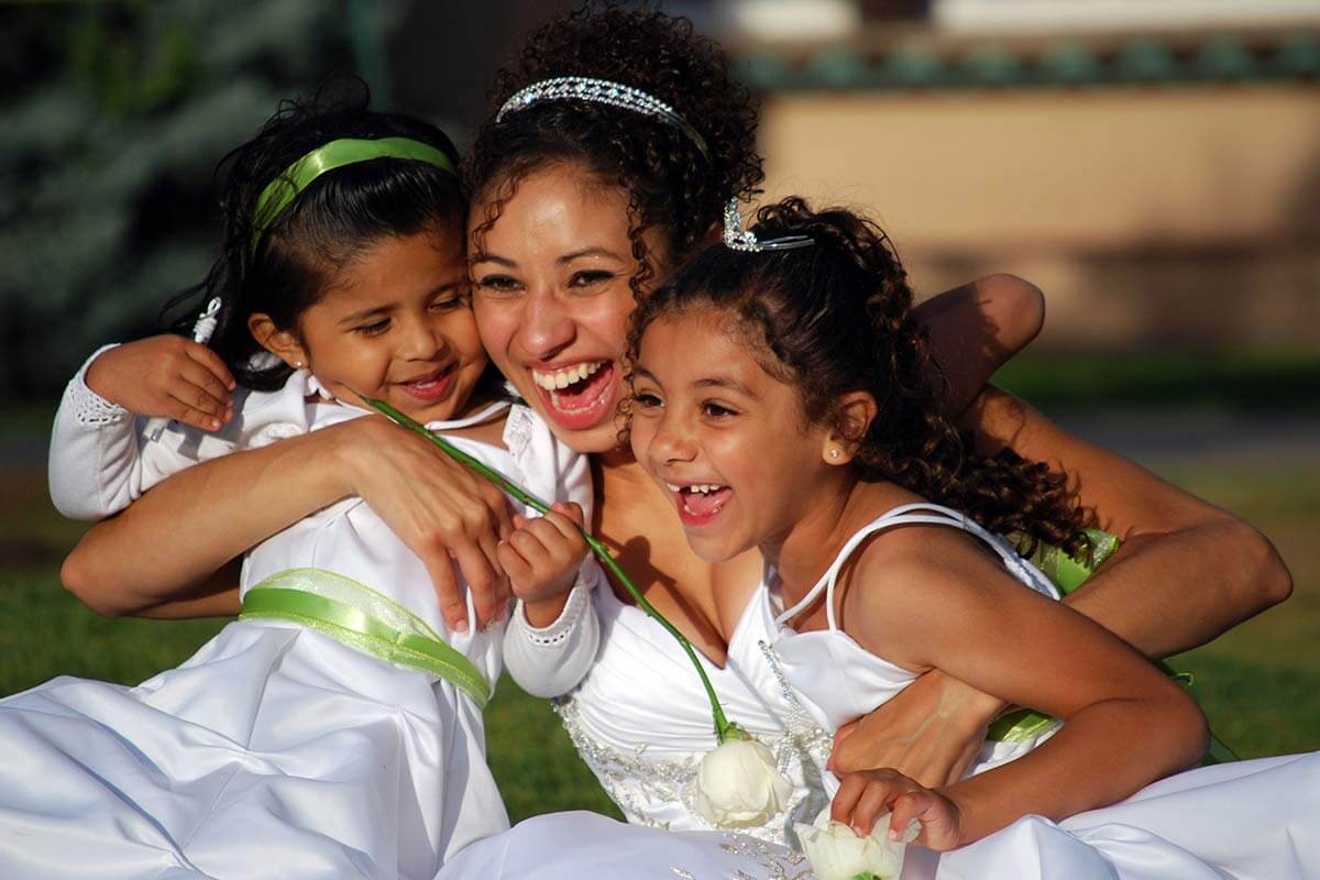 smiling bride hugging two young girls
