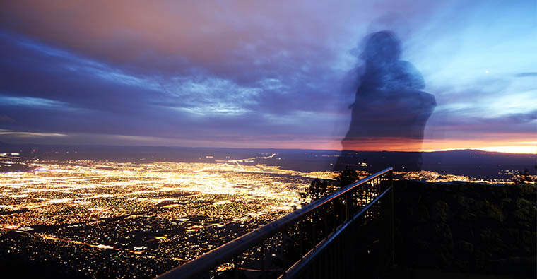silhouette of a person standing on the Sandia Mountains overlooking city lights