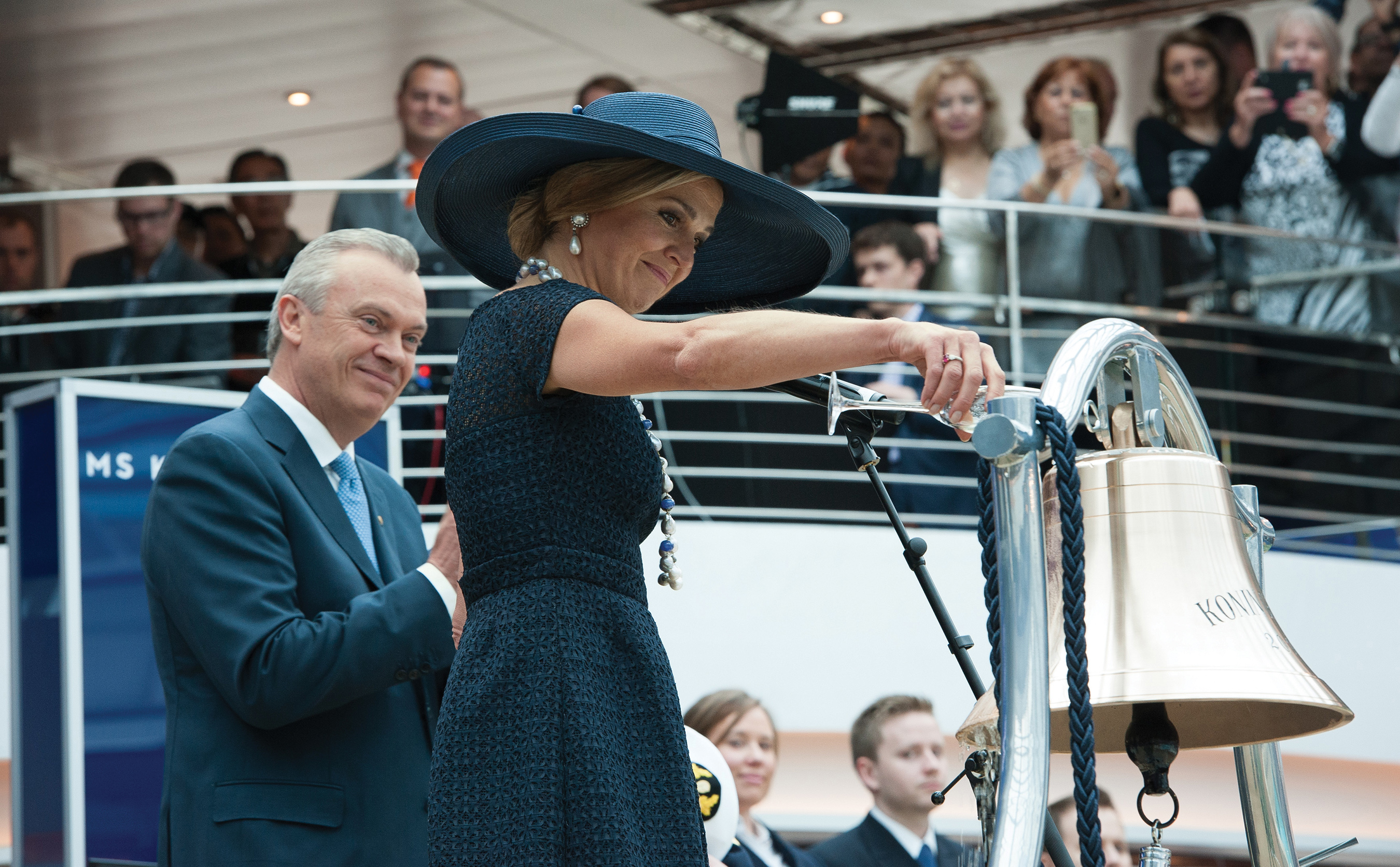 Her Majesty Queen Máxima performs the ceremonial honors of blessing the ship's bell in the Lido pool area by pouring a glass of champagne over the bell while Holland America Group CEO Stein Kruse watches.