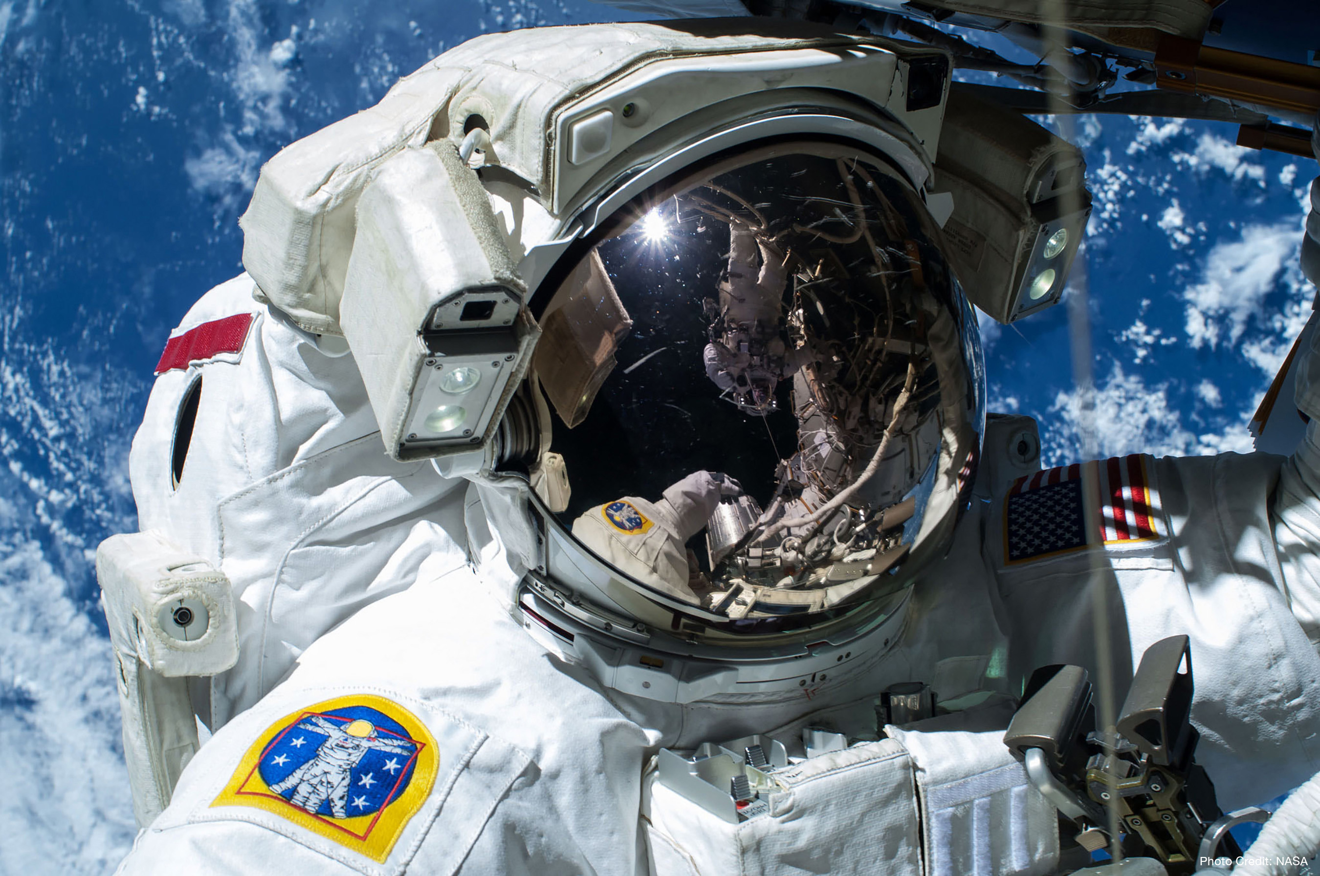 "NASA astronaut Barry ""Butch"" Wilmore, Commander of Expedition 42 is caught by the camera during a spacewalk on Feb. 21, 2015, as the Earth's surface passes by in the background. Photo credit: NASA."