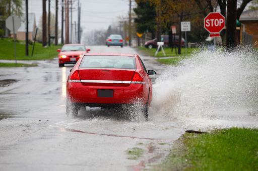 Car splashing through puddle on one side