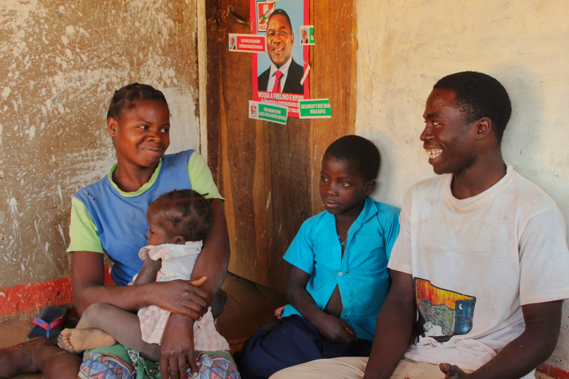 A husband and wife, who are farmers, sit with their children in the home in Mozambique. This family participated in CGAP's Smallholder Diaries. Photo by Erin Scronce