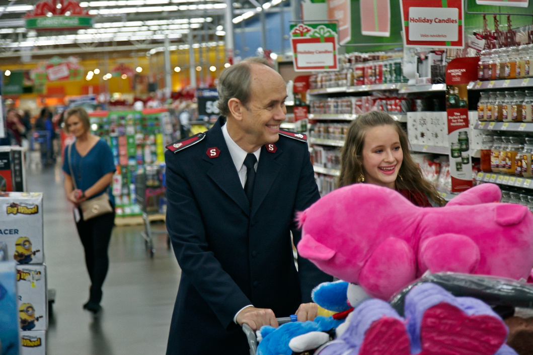 Maddie and Lt. Col. Ron Busroe fill their shopping cart to the brim with gifts and toys.