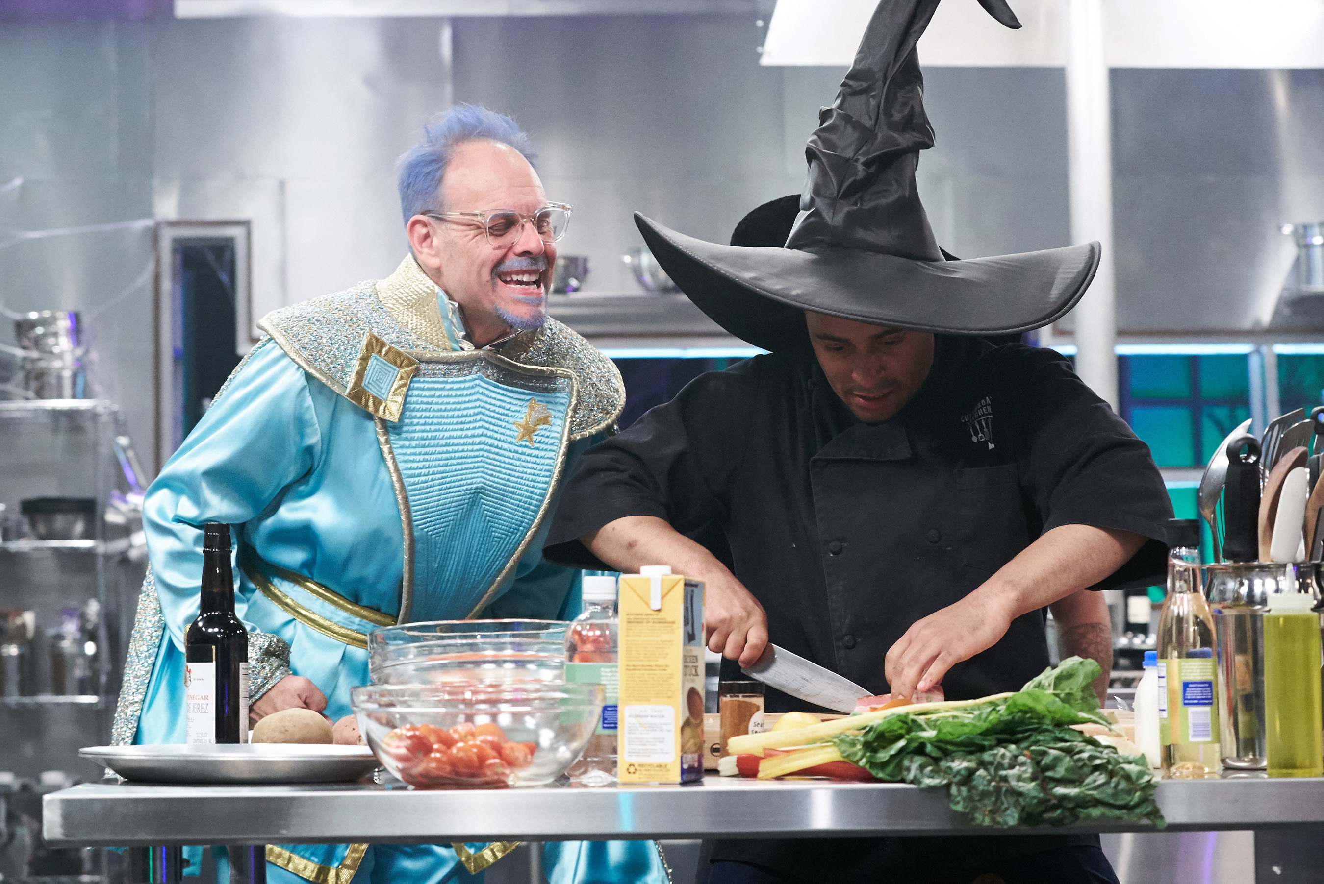 Host Alton Brown watches Chef Michael Jenkins on Food Network's Cutthroat Kitchen: Tournament of Terror