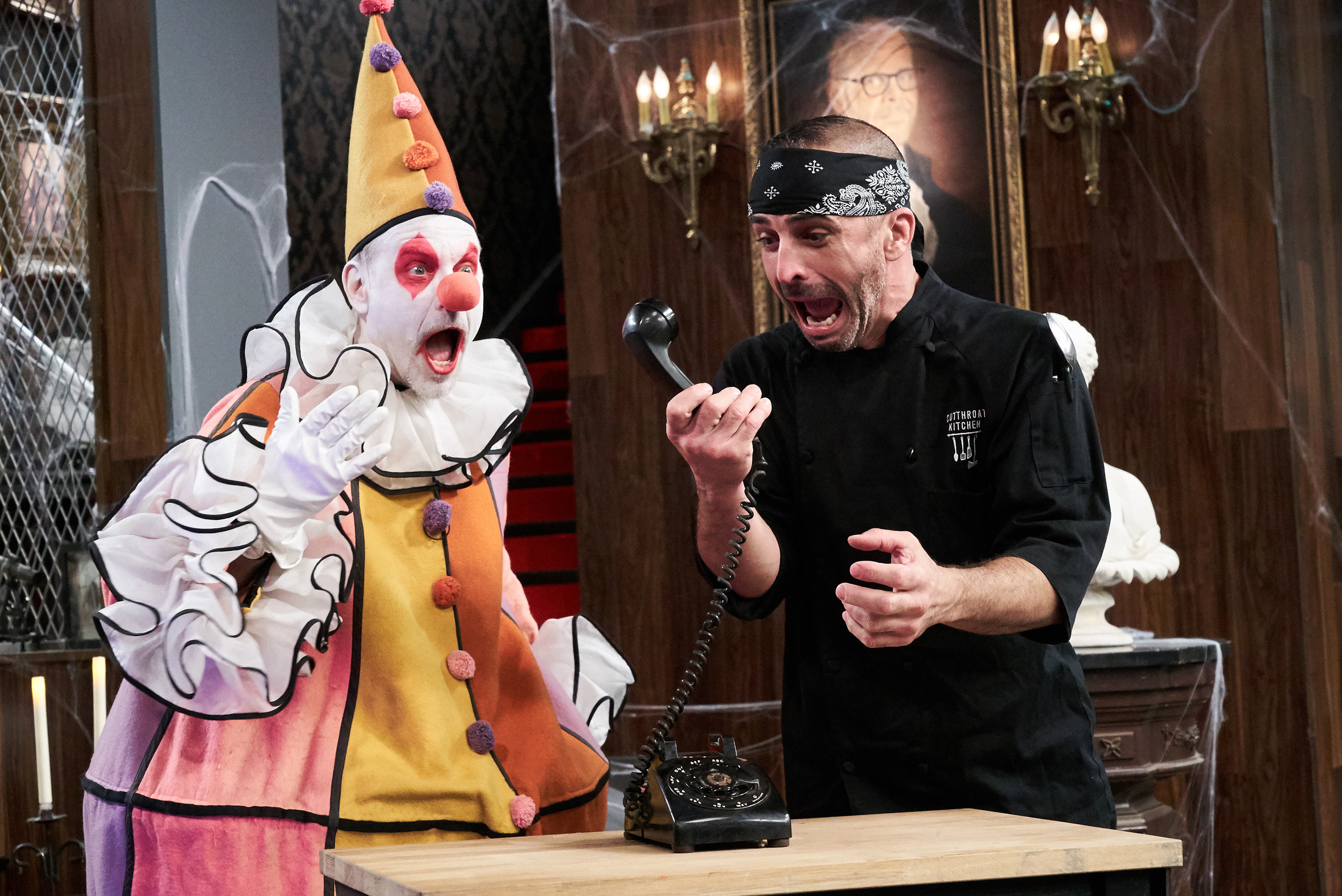 Host Alton Brown with contestant Johnny Messina on Food Network's Cutthroat Kitchen: Tournament of Terror