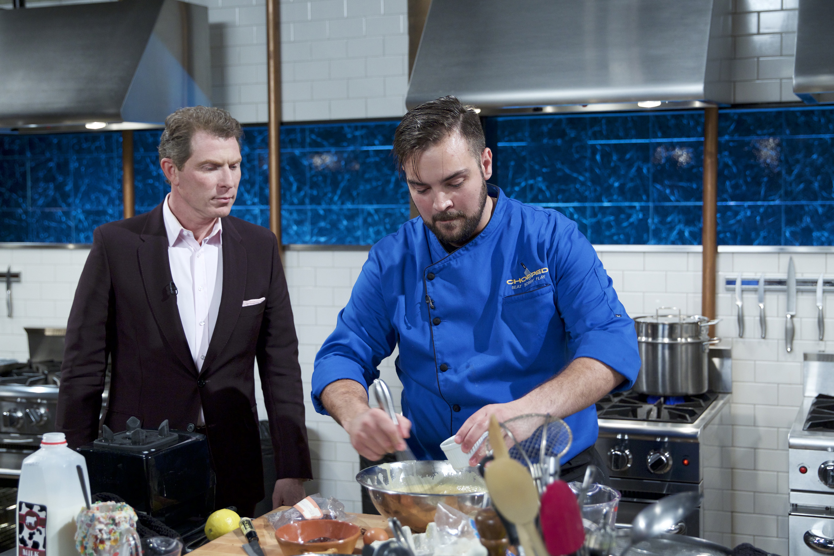 Judge Bobby Flay checks in on a competitor on Food Network's Chopped: Beat Bobby Flay