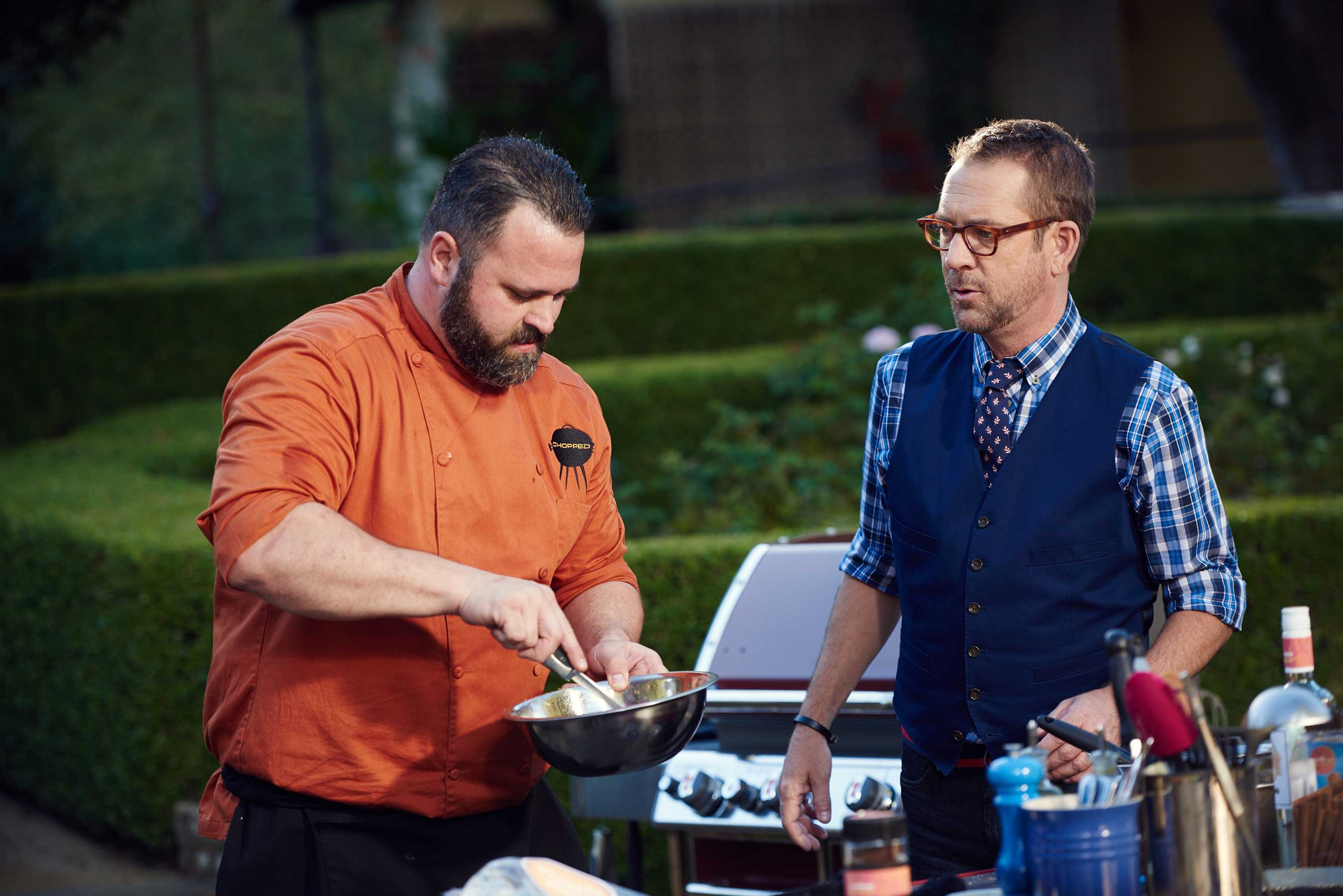 Host Ted Allen watches competitor Jason Bergeron on Food Network's Chopped Grill Masters Napa.