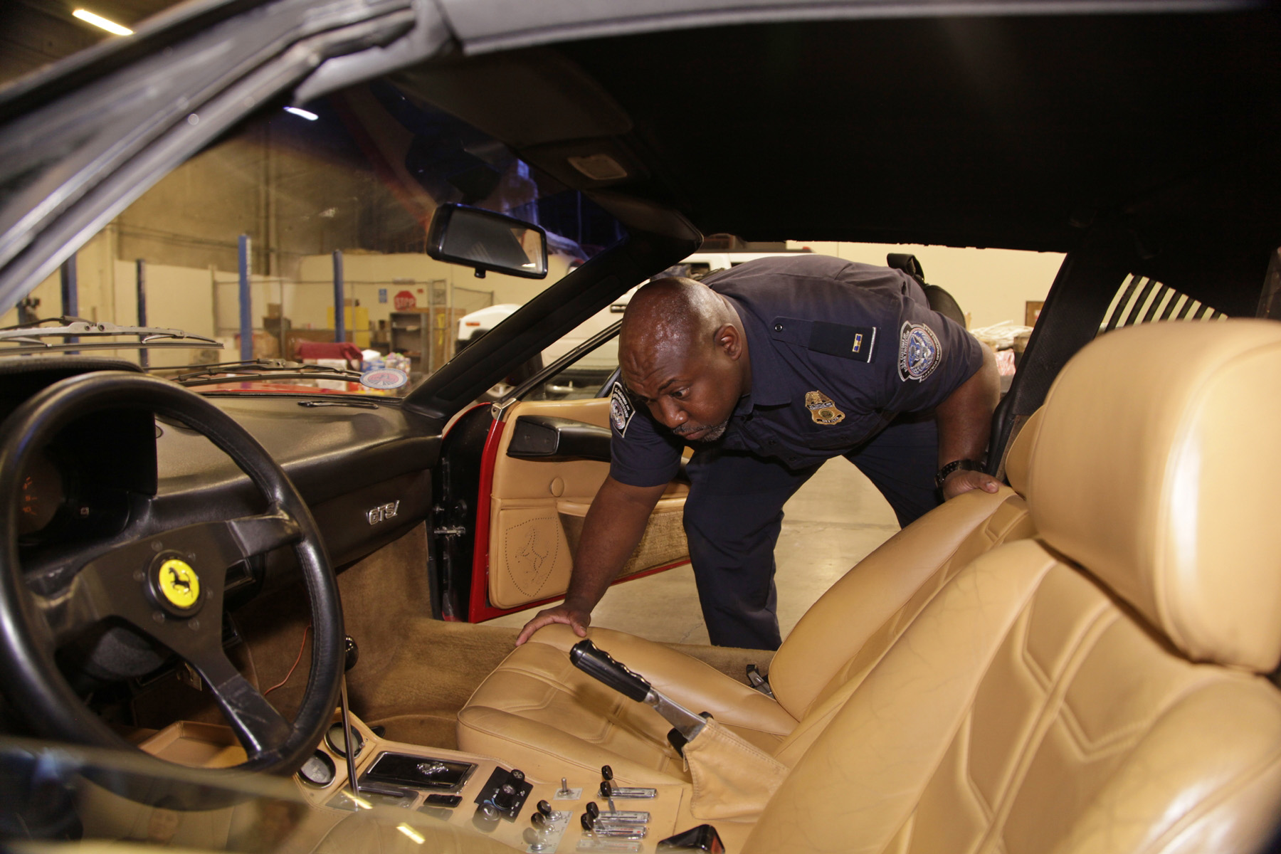 A Customs and Border Protection Officer inspects the interior of the stolen Ferrari