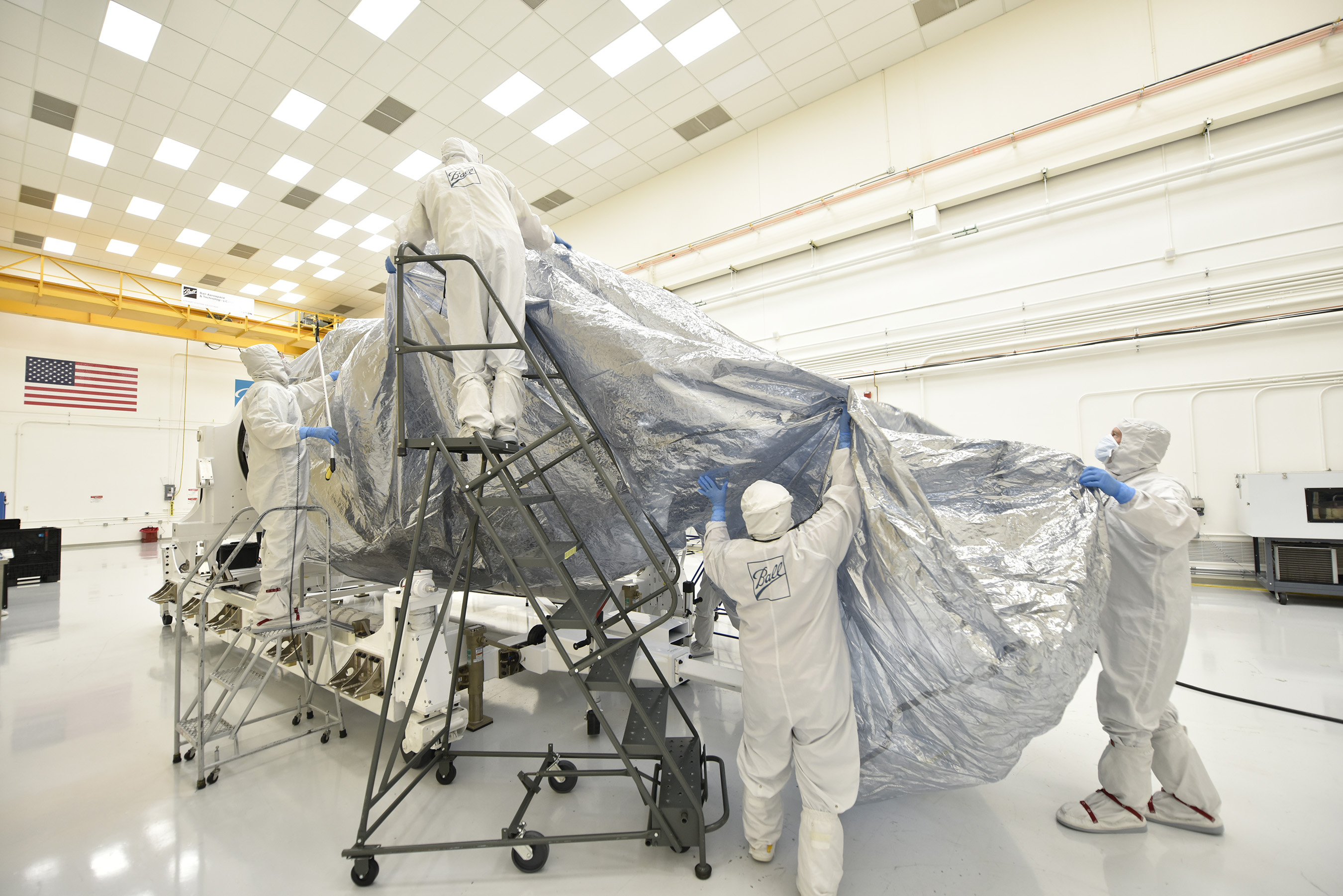 The Ball Aerospace team begins bagging the JPSS-1 satellite with protective wrapping in preparation for its shipment from the Ball Aerospace cleanroom in Boulder, Colo., to Vandenberg Air Force Base for final launch preparations. CREDIT: Ball Aerospace.