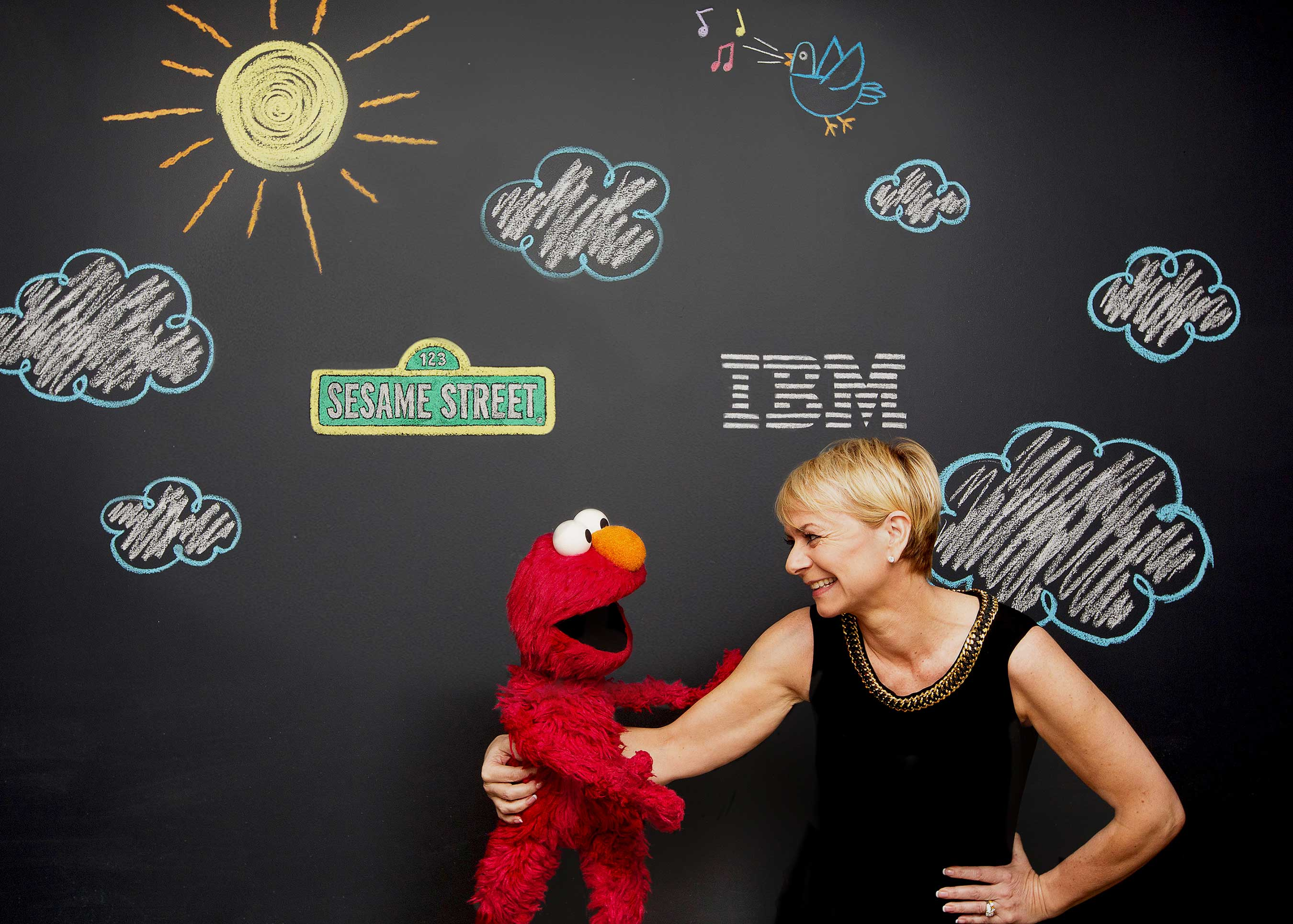 As part of a three-year agreement, Sesame Workshop and IBM Watson are developing a new category of educational products that aim to adapt to the learning styles and aptitudes of individual preschoolers. Pictured here are Harriet Green, IBM General Manager of Watson Internet of Things, Commerce and Education, and Elmo, 3 1/2 year old monster. (John O'Boyle, Feature Photo Service for IBM)